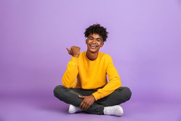 Ritratto di allegro ragazzo americano sorridente e puntando il dito da parte a copyspace, mentre è seduto sul pavimento con le gambe incrociate, isolato su sfondo viola