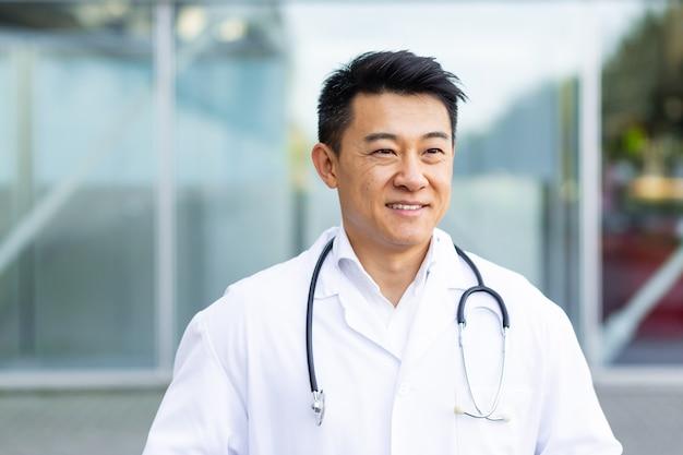 Ritratto di un allegro medico asiatico che sorride sullo sfondo di una moderna clinica all'aperto