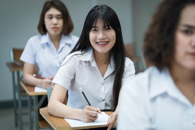 Ritratto di studentesse universitarie asiatiche allegre che scrivono e studiano in classe. quattro studenti universitari adolescenti selettivi che studiano in classe.