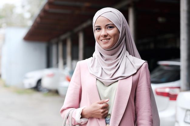 Ritratto di allegra attraente giovane donna musulmana in velo rosa in piedi contro il parcheggio all'aperto