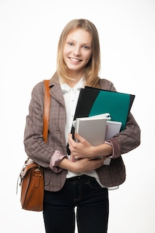 Ritratto di una giovane donna attraente allegra dello studente con i libri della tenuta della borsa.