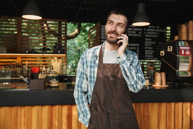 Ritratto di un allegro barista che indossa un grembiule che sorride e parla al cellulare in un caffè di strada o in un caffè all'aperto