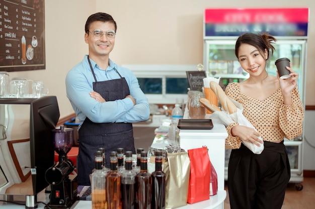 Ritratto di baristi allegri che sorridono nella caffetteria