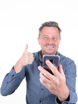 Il ritratto dell'uomo barbuto allegro che prende il selfie che mostra i pollici aumenta il gesto sopra fondo bianco