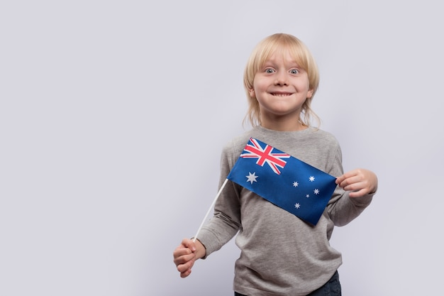 Ritratto del ragazzo biondo allegro con la bandiera australiana a disposizione su spazio bianco