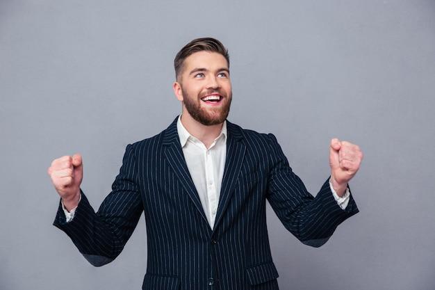 Ritratto di un uomo d'affari allegro che celebra il suo successo sul muro grigio