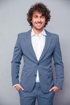 Ritratto di un uomo d'affari allegro in piedi sopra il muro grigio