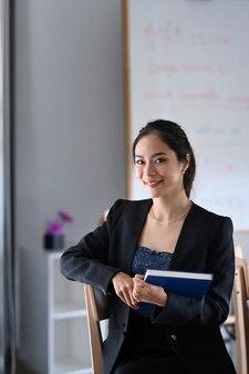 Ritratto di allegro imprenditrice tenendo il libro e seduto in un ufficio moderno