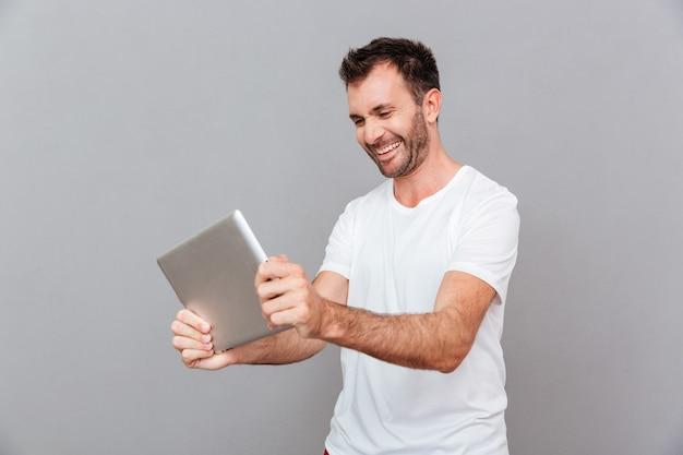 Ritratto di un uomo casual allegro che utilizza un computer tablet su sfondo grigio