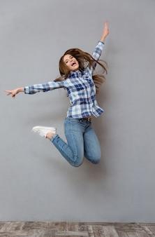 Ritratto di una donna casual allegra che salta sul muro grigio gray
