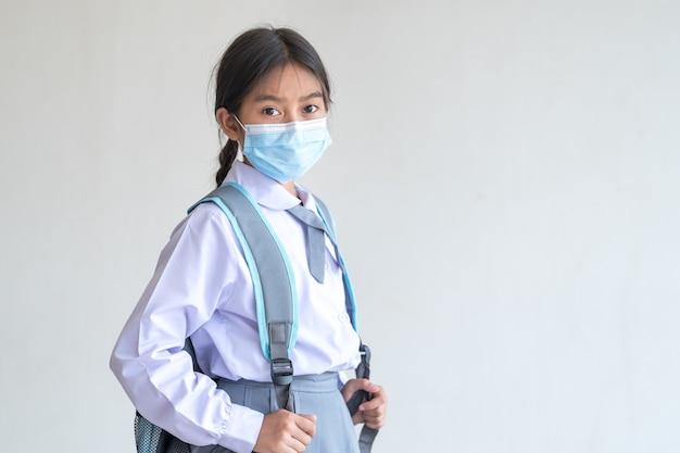 Ritratto di uno studente allegro bambino indossa una maschera facciale isolata su sfondo bianco sorride e guarda la telecamera. torna al concetto di scuola stock photo