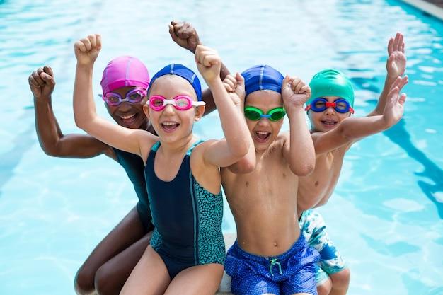 Ritratto di bambini allegri che godono a bordo piscina