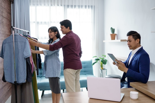 Un ritratto di una coppia allegra che sceglie e compra vestiti. al negozio di vestiti