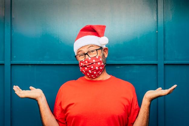 Ritratto di uomo adulto allegro e desolato con cappello rosso santa e maschera facciale per emergenza virus covid-19 coronavirus virus