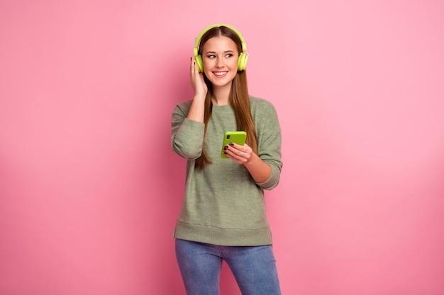 Il ritratto della ragazza eccitata allegra usa lo smartphone ascolta la musica