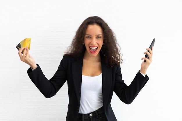 Ritratto allegro eccitato latino business donna modello capelli ricci tenendo la carta di credito e smartphone a portata di mano.