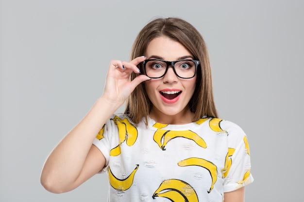 Ritratto di un'adolescente allegra con gli occhiali che guarda la telecamera isolata su uno sfondo bianco