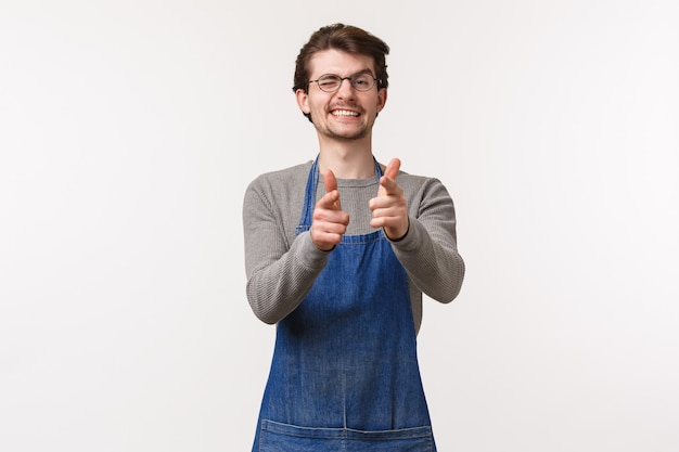 Ritratto di allegro uomo amichevole in grembiule, lavoro al bar o al ristorante, mostra il segno di saluto informale pistole con le dita che indicano e ammiccano, invitando a visitare il suo negozio, muro bianco