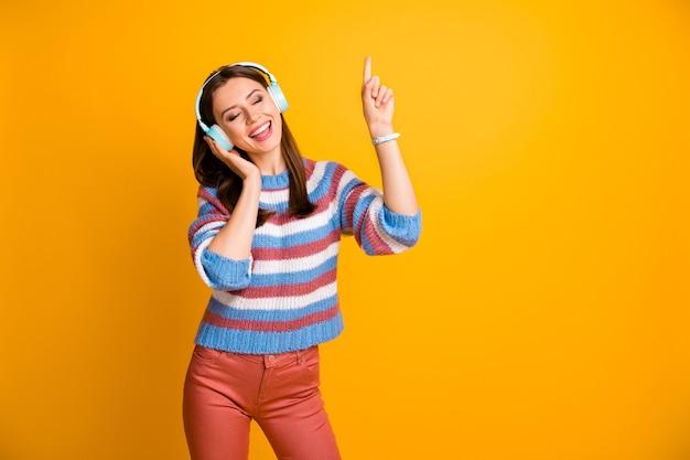 Il ritratto della ragazza allegra ha auricolare godere di ascoltare la musica della radio