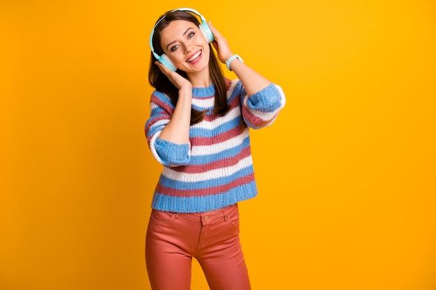Il ritratto della ragazza allegra ha auricolare senza fili ascolta la musica radiofonica godere