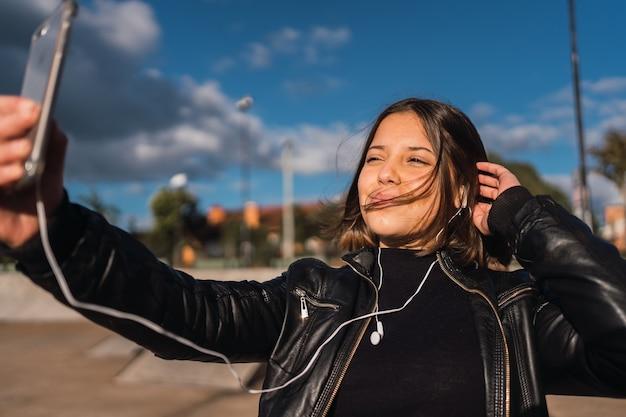 Ritratto di una ragazza allegra che prende un selfie all'aperto.