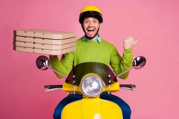 Ritratto del ragazzo allegro che guida il ciclomotore che porta il lato del dito diretto della pizza