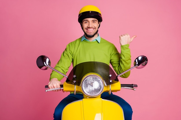 Ritratto di allegro ragazzo in sella a ciclomotore che mostra annuncio