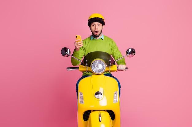 Ritratto di ragazzo allegro in sella a una moto utilizzando post sul blog di lettura delle cellule