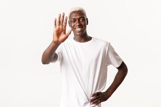 Ritratto di allegro bel ragazzo biondo afro-americano, sorridendo soddisfatto e tendendo la mano per il cinque