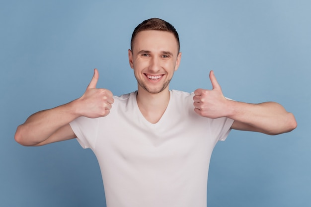 Il ritratto di un bel ragazzo allegro mostra due braccia con il pollice in alto sorriso raggiante isolato su sfondo di colore blu