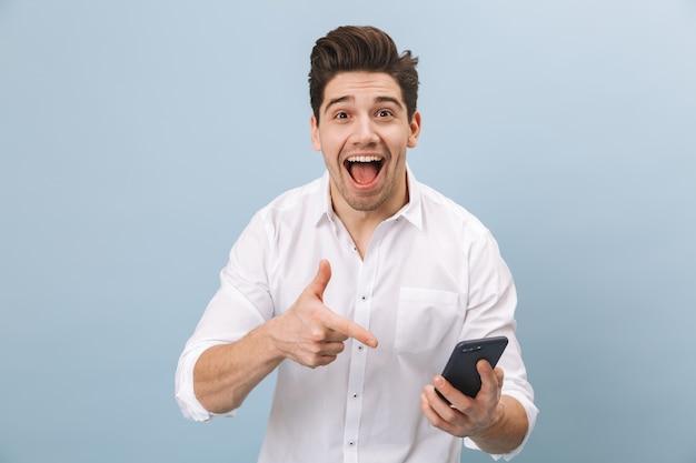 Ritratto di un allegro bel giovane uomo in piedi isolato su blu, tenendo il telefono cellulare, celebrando