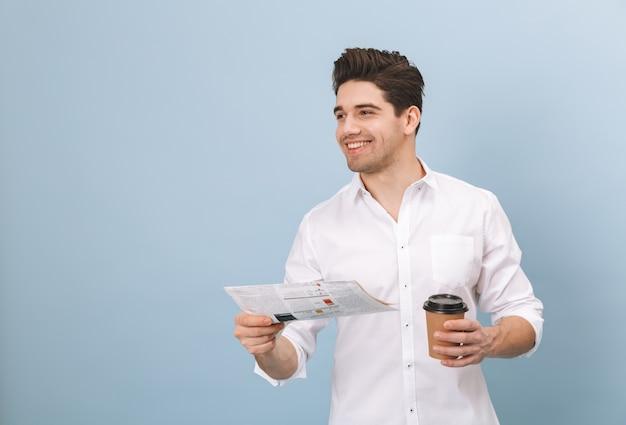 Ritratto di un allegro bel giovane uomo in piedi isolato su blu, tenendo la tazza di caffè da asporto, leggendo il giornale