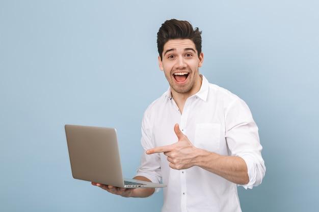Ritratto di un allegro bel giovane uomo in piedi isolato su blu, lavorando su un computer portatile