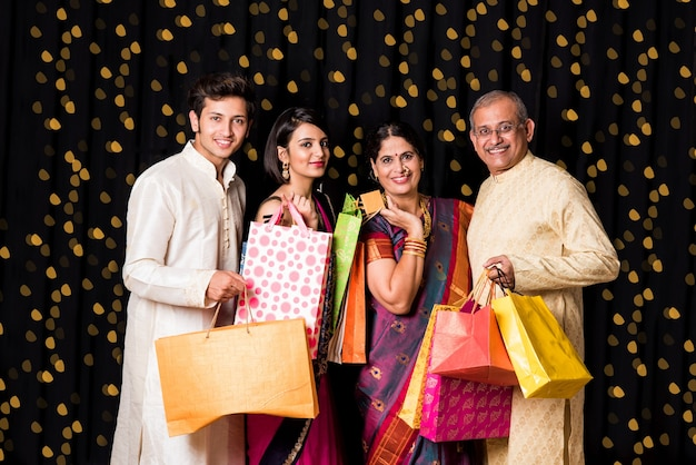 Ritratto di allegra famiglia indiana con borse della spesa in abbigliamento tradizionale a diwali isolate su sfondo nero con bokeh