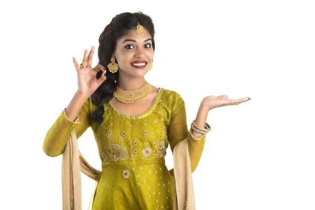 Ritratto di giovane donna indiana tradizionale allegra che presenta qualcosa, mostrando lo spazio della copia sul suo palmo su bianco