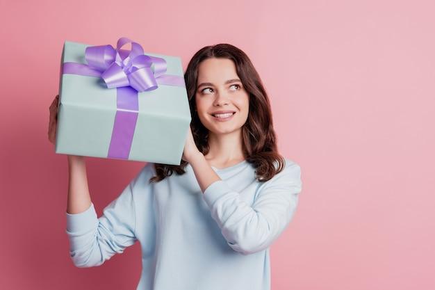 Ritratto di una ragazza allegra e interessata che tiene in mano una scatola che sembra uno spazio vuoto