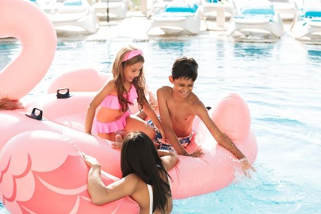 Ritratto di bambini allegri e genitori che si divertono mentre nuotano in piscina con anello di gomma rosa, fuori dall'hotel durante le vacanze