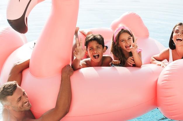 Ritratto di bambini allegri e genitori che nuotano in piscina con anello di gomma rosa, fuori dall'hotel durante le vacanze