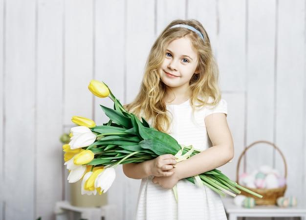 Ritratto di piccola ragazza bionda allegra con il mazzo dei tulipani su fondo di legno bianco.