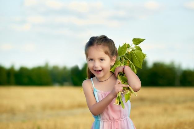 Ritratto di una bambina carina allegra in un abito estivo con un mazzo di fiori nelle sue mani camminando lungo un campo fuori città in una calda sera d'estate
