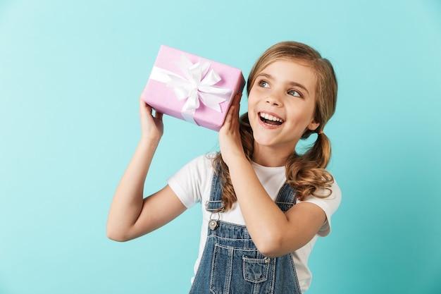 Ritratto di una bambina allegra isolata sul muro blu, che mostra la scatola attuale