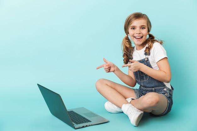 Ritratto di una bambina allegra isolata sul muro blu, che studia con un computer portatile, che punta il dito