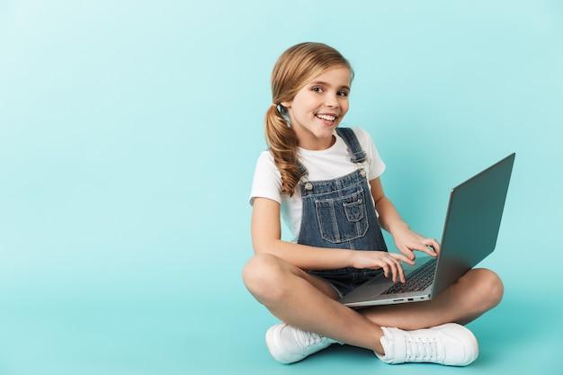 Ritratto di una bambina allegra isolata sul muro blu, che studia con un computer portatile
