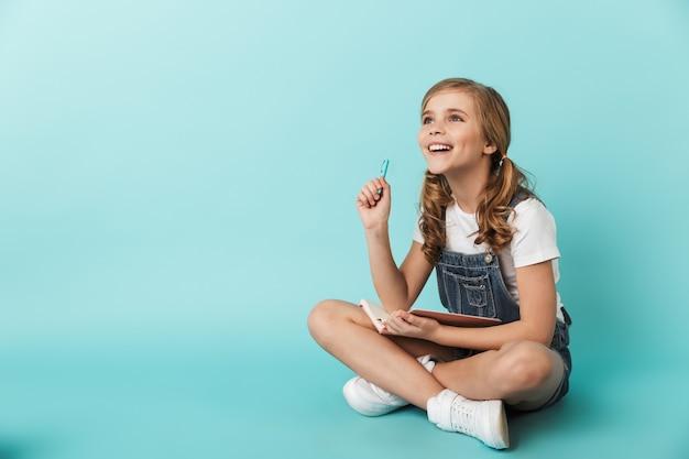 Ritratto di una bambina allegra isolata sul muro blu, che scrive su un taccuino