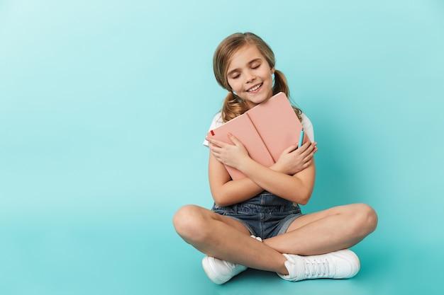 Ritratto di una bambina allegra seduta isolata sul muro blu, con in mano un libro