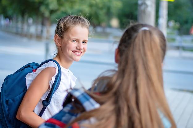 Ritratto di una bambina allegra che parla con un'altra ragazza.