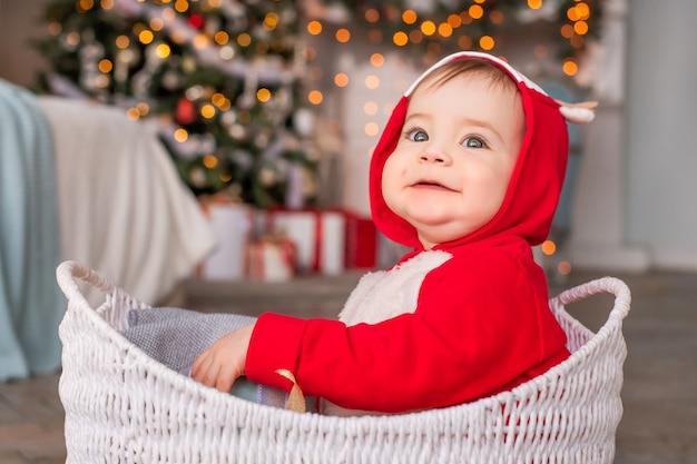 Ritratto di un allegro ragazzino in costume da renna rossa di babbo natale seduto nel cesto sullo sfondo dell'albero di natale