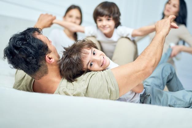 Ritratto di allegro ragazzino latino che sorride alla macchina fotografica, giocando con i suoi genitori e fratelli su un letto a casa. infanzia felice, concetto di genitorialità