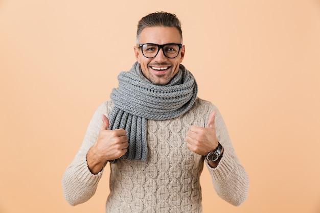 Ritratto di un uomo allegro vestito in maglione e sciarpa in piedi isolato sul muro beige, dando pollice in alto