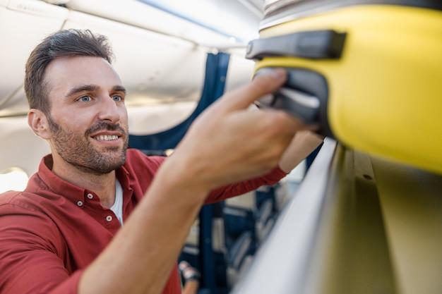 Ritratto di uomo allegro che estrae la valigia dal vano bagagli a mano, armadietto sopraelevato durante il viaggio in aereo. vacanza, concetto di trasporto